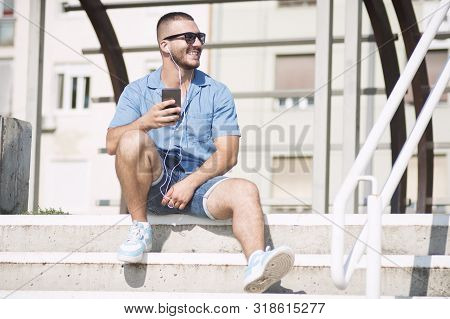 The Smiling Young Guy With Earphones Is Sitting On Steps And Using Phone Outdoors.