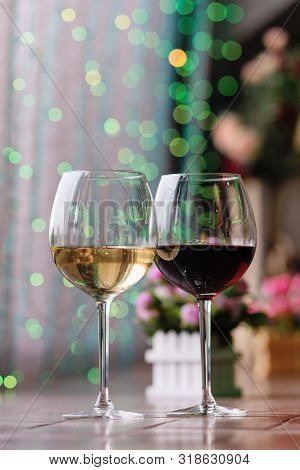 Two Glasses Of Wine White And Red Standing On A Table. Colorful Bokeh. Wine Tastings, Wine Tour. Col