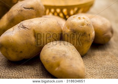 Close Up Shot Of Potato Or Aloo Or Alu On Jute Bag Surface Along With Two Vegetable And Fruit Hamper