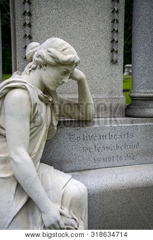 A Marble Lady Sits Grieving In An Old Cemetery