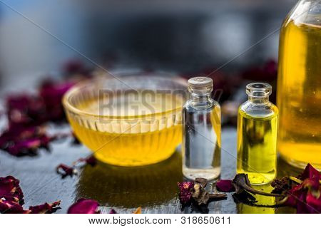 Close Up Of Castor Oil, Tea Tree Oil, And Some Coconut Oil In Bottles On The Wooden Surface Along Wi