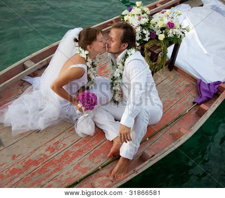young couple in wedding dress kissing in the boat