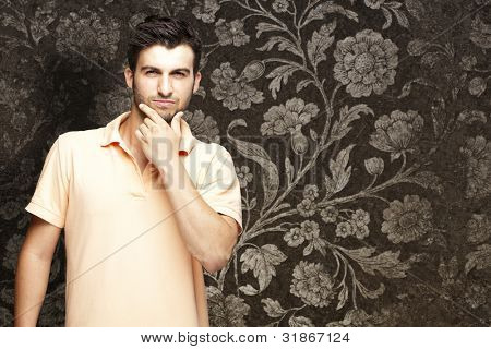 portrait of young man thinking against a vintage wall