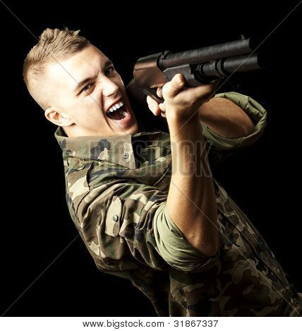 portrait of a young soldier aiming with shotgun against a black background