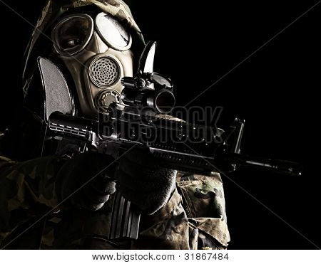 soldier with camouflage coat, rifle and gas mask over black