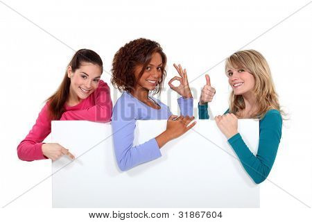 Women enthusiastically holding up a blank sign poster