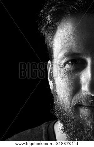 Black And White,half Portrait Of A Man Close Up Looking At Camera On Black Background