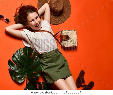 top view of a pretty undergrow girl in a business T-shirt and khaki skirts on a terracotta background gets pleasure and pleasure to lie down to rest. Boho accessories. poster