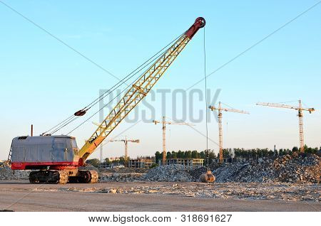 Large crawler crane or dragline excavator with a heavy metal wrecking ball on a steel cable. Wrecking balls at construction sites. Dismantling and demolition of buildings and structures - Image poster