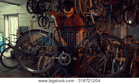 Theme Small Business Bike Repair. Young Caucasian Brunette Man Wearing Safety Goggles, Gloves And Ap