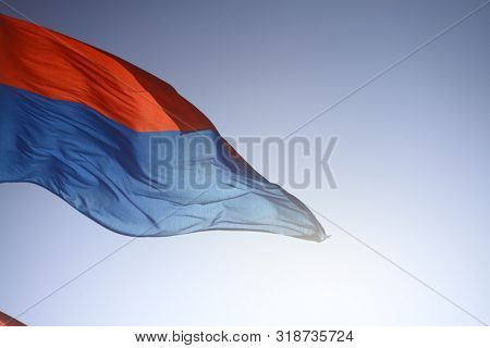 The flag of the Swiss Canton of Ticino fluttering in the wind against a clear blue sky