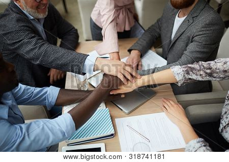High Angle Closeup Of Diverse Business Team Stacking Hands While Huddling Over Meeting Table In Offi