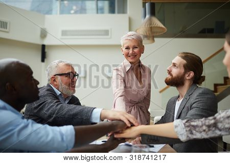 Portrait Of Diverse Business Team Stacking Hands While Huddling Over Meeting Table In Office, Copy S