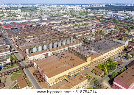 Aerial Top View Of Urban Industrial District. Roofs Of Factory Buildings And Warehouses