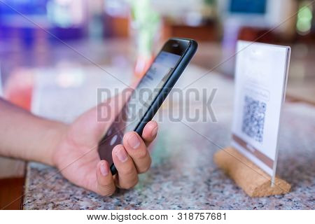 Closeup Of A Hand Holding Phone And Scanning Qr Code. Man Hand Paying With Qr Code.