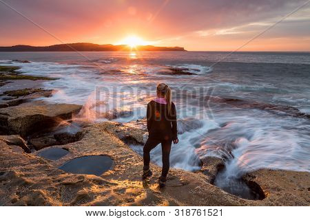 Sunflare Kissing The Shoulder Of A Woman Standing  By The Rocky Coastal Shore Watching The Sunrise