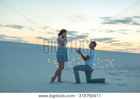 The Guy Makes The Girl A Marriage Proposal By Bending His Knee While Standing On The Sand In The Des
