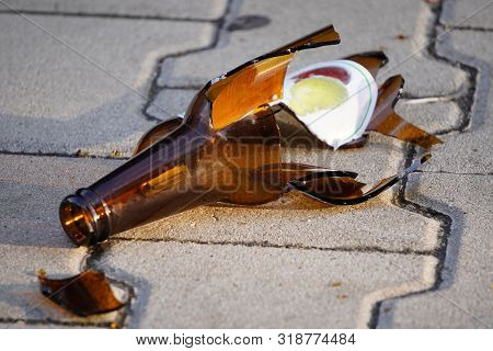 Bottle Of Beer, Soda Or Drugs From Dark Glass Is Broken. Shattered Beer Bottle On Ground In Sunset L