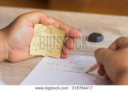 Student Using Formula Math Sheet To Cheat On Test. Hand Of University Student Holding Pencil Doing M