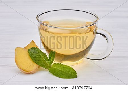 Cup Of Tea With Ginger And Mint. Glass Transparent Cup Of Green Tea With Ginger And Mint Leaves On W