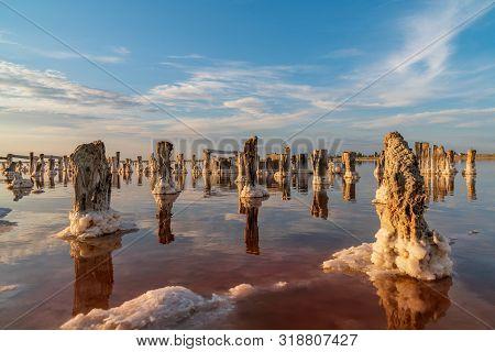 Sunset On The Salt Lake. Brine, Salt And Wooden Pegs.extraction Of Salt.