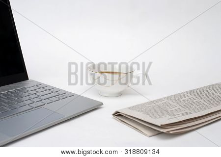 Laptop, Fresh Newspaper And Hot Coffee On White Background, White Desk Of Office Worker, Financial C