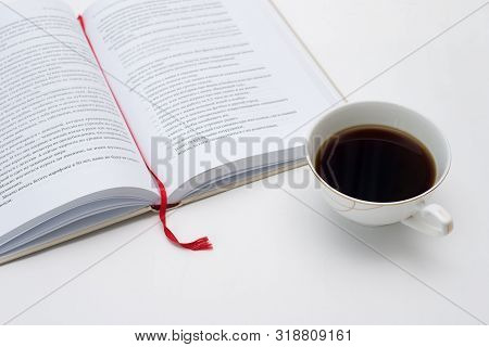 Open Book With Red Bookmark Is Next To A Mug Of Black Coffee White Background