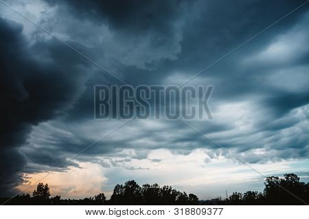 Dramatic Cloudscape. Sunny Light Through Dark Heavy Thunderstorm Clouds Before Rain. Overcast Rainy