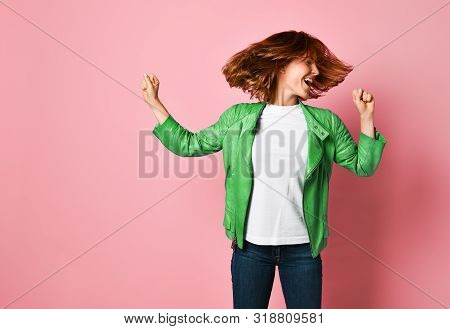 Young Woman Wearing Jeans And A Jacket Is Shaking Her Head With Her Hair. The Concept Of Joy, Happin