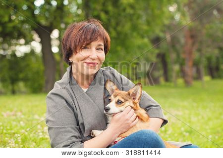Portrait Of Cute Happy Mature Woman With Puppy Dog Pet In Summer Park