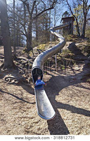 Boy Sliding On A Big, Steep, Metal Slide In Slottsskogen Park, Gothenburg, Sweden