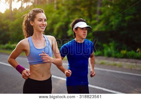 Fitness Sport Couple Running Jogging Outside Asphalt Road Pine Forest Nature Landscape. Runners Trai