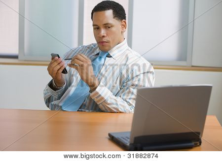 African American businessman at desk with palm pilot and laptop