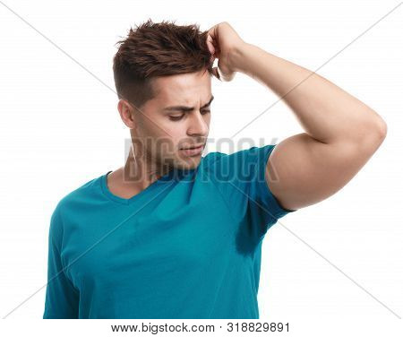 Young Man With Sweat Stain On His Clothes Against White Background. Using Deodorant