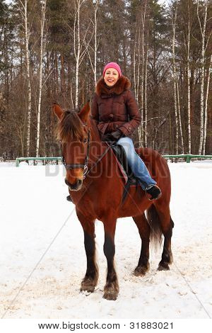 Beautiful young woman sits on brown horse and smiles at winter