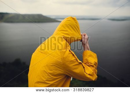 Traveler In Yellow Raincoat Standing On Cliff And Looking At Lake In Rainy Windy Day. Wanderlust And