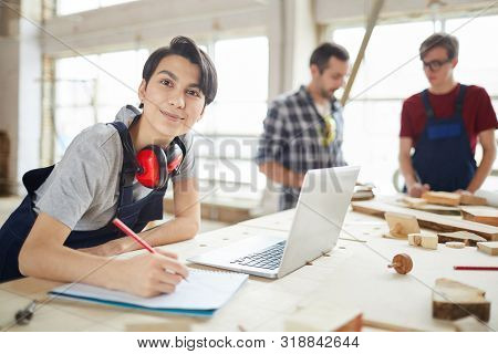 Portrait Of Modern Carpenters Working At Woodworking Factory, Focus On Young Woman Smiling At Camera