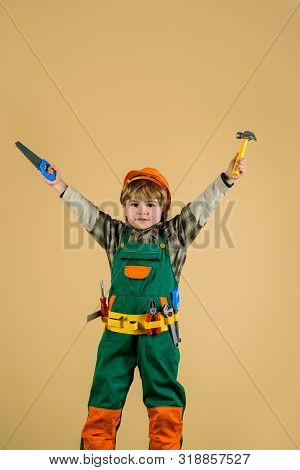 Cute Little Builder In Hard Hat With Hammer, Saw. Little Boy In Builders Uniform With Tools. Little