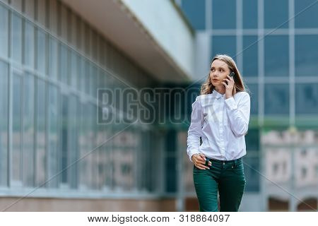 Young Famale Calling On A Smartphone And Walking On Street. Attractive Businesswoman Talking By Phon