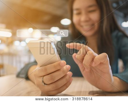 The Girl Smiles And Uses A Smartphone To Find What You Are Interested. Searching Information Data On
