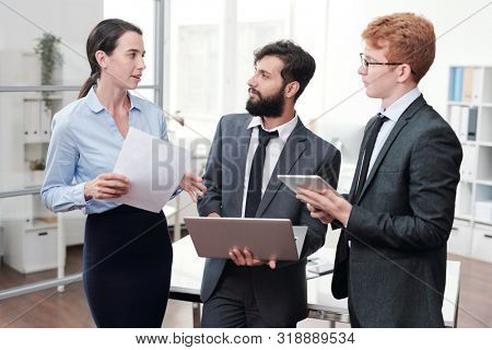 Portrait of three young business people discussing work and smiling while standing in modern office