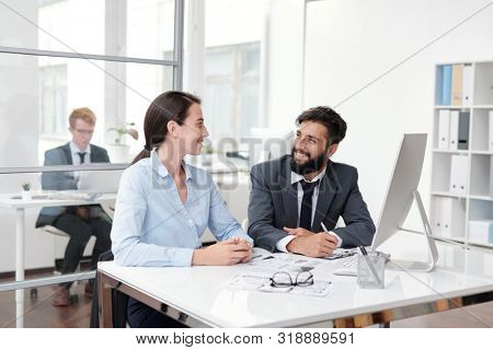 Portrait of two colleagues looking at each other and smiling while sitting at desk in office, copy space