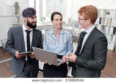 Portrait of three young business people discussing work and smiling while standing in modern office, copy space
