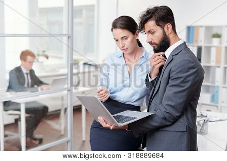Waist up portrait of two business colleagues using laptop while standing in modern office, copy space