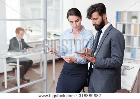 Portrait of two young business people, man and woman, suing tablet together while working in office, copy space