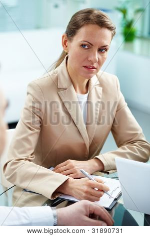 Vertical portrait of a serious businesswoman taking notes
