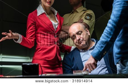 Middle-aged defendant using the right to remain in silence while listening to the charges of the prosecution during an aggressive interrogation at the police