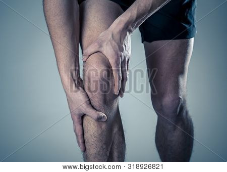 Sport Man Injured When Exercising Or Running Holding His Knee In Pain