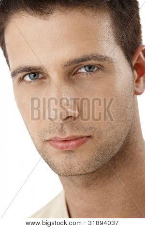 Closeup portrait of handsome young man looking at camera confidently.