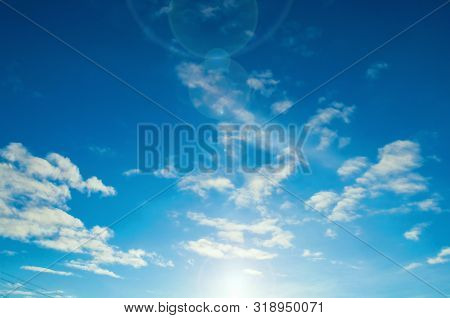 Blue dramatic sunset sky background - picturesque colorful sky clouds lit by sunlight. Vast sky landscape panoramic scene, sunset sunny sky view